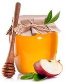 Latta di vetro in pieno di miele, della metà della mela e del bastone di legno Immagine Stock