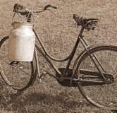 Lattaio anziano della bicicletta con il recipiente di alluminio per il trasporto del latte Immagine Stock Libera da Diritti