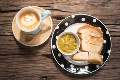 Latte και κέικ σε έναν ξύλινο πίνακα στον καφέ Στοκ Φωτογραφία