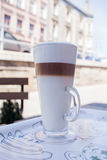Latte στο φλυτζάνι γυαλιού στο ζωηρόχρωμο δίσκο κλείστε επάνω ανασκόπηση αστική Στοκ φωτογραφία με δικαίωμα ελεύθερης χρήσης