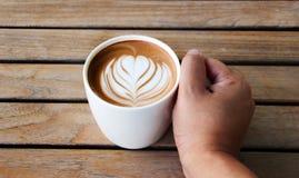 latte искусства кофейной чашки владением руки Стоковое фото RF