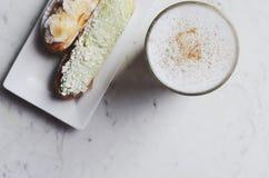 Latte и eclairs с космосом экземпляра на мраморной предпосылке Стоковое фото RF