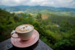 Latte кофе в белой чашке на пребывании плиты на крылечке с горным видом и облачным небом Стоковые Фото
