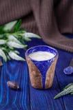 Latte кофе, темная конфета шоколада и белые цветки на голубой предпосылке открытый космос Стоковые Фото