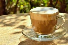 Latte на мешковине покрыл таблицу в стеклянной чашке Стоковая Фотография RF