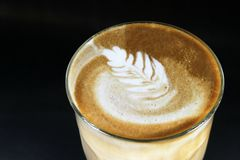 Latte. A double latte in a tall latte glass with latte art Stock Photos