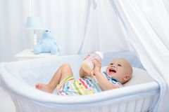 Latte alimentare del bambino Il ragazzo con la formula imbottiglia il letto Fotografie Stock Libere da Diritti