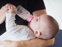 Latte alimentare del neonato dalla bottiglia a casa Fotografia Stock