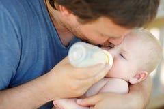 Latte alimentare del piccolo neonato dalla bottiglia Immagini Stock