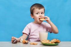 Latte alimentare del ragazzino sveglio e biscotti di cibo fotografie stock