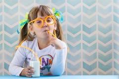 Latte alimentare della ragazza divertente del bambino con la paglia di vetro su backgr blu immagine stock
