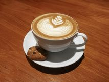 Latte art with biscuit on wooden table. Beautiful heart shapes Latte art with biscuit on wooden table royalty free stock photography