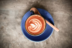 Latte art, Blue coffee cup on wood Royalty Free Stock Image