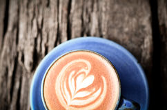 Latte art, Blue coffee cup on wood Stock Photography