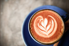 Latte art, Blue coffee cup on wood Royalty Free Stock Photo