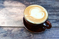 Latte art on a cappucinno , on wooden table Stock Photo