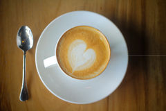 Latte art on a cappucinno , on wooden table Royalty Free Stock Photography