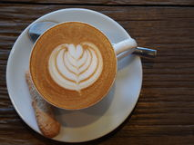 Latte art coffee and biscuit Royalty Free Stock Images