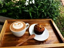 Latte art coffee and Chocolate cup cake. Latte art coffee, wood spoon and Banana Chocolate cup cake on the wooden tray Green Background royalty free stock image