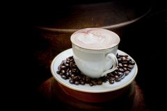 Latte art, coffee in coffee beans and Asian pottery background Stock Photography