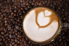 Latte art, coffee in coffee beans background Stock Photos