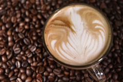 Latte art, coffee in coffee beans background Royalty Free Stock Photos