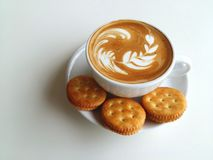 Latte art coffee and cracker so delicious on white. Latte art coffee with coffee bean and cracker so delicious on white Royalty Free Stock Photos