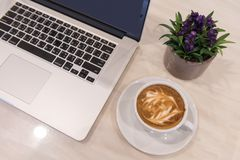 Latte art coffee cup with laptop computer and plants. Vase on table stock photos
