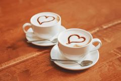 Latte art coffee cups with hearts on table in cafe stock image