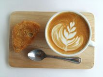 Latte art coffee so delicious on white. Latte art coffee and cracker so delicious on white Royalty Free Stock Image