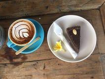Latte Art Coffee nella tazza del turchese, nel dolce di cioccolato ed in un fiore immagini stock