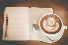 Latte art coffee and notebook on the table at restaurant Royalty Free Stock Photography