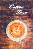 Latte art:Coffee time concept with hot coffee in white cup on wooden table. Latte art:Coffee time text with hot coffee in white cup on wooden table Royalty Free Stock Photos