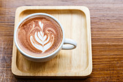 Latte art coffee in a white cup on wooden table, top view Stock Photos