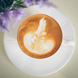 Latte art. A cup of latte coffee in a white cup, see purple flower as foreground Stock Photos