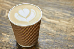 Latte art in paper cup. Coffee foam flower symbol Royalty Free Stock Images