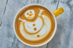Latte art snowman. Coffee cup top view Stock Image