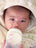 Latte asiatico del bambino che si alimenta silenziosamente con il copricapo Fotografia Stock