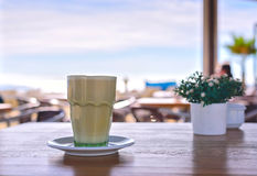 Latte at the beach. Iced Coffee Frappuccino or frappe in a tall glass. Sea view background Barcelona Spain Stock Photo