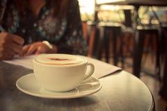 Latte bevente della giovane donna d'annata di immagine alla caffetteria Gi Fotografia Stock