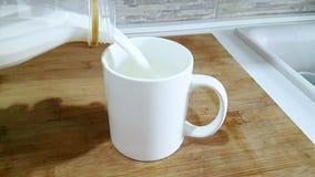 Latte bianco fresco che versa nel bicchiere sul fondo della cucina, sparante con il movimento lento, la dieta e la nutrizione san video d archivio