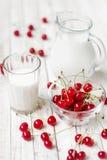 Latte bianco in un vetro ed in una brocca su un fondo bianco Fotografie Stock Libere da Diritti