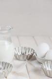 Latte-brocca, uova e piatto di cottura su un fondo bianco Immagine Stock Libera da Diritti