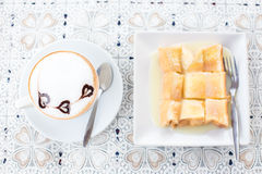 latte caliente de la moca del café en la taza y el pan blancos en el fondo de madera Imagenes de archivo