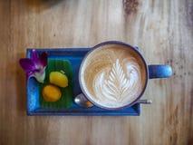 Latte caliente del café con la decoración tailandesa del estilo con la orquídea foto de archivo libre de regalías