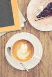 Latte caliente del café con la forma de vida azul o del ocio del pastel de queso de la baya Imagen de archivo
