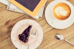 Latte caliente del café con la forma de vida azul o del ocio del pastel de queso de la baya Fotos de archivo libres de regalías
