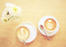 Latte or cappuccino coffee and flower with retro filter e Stock Images