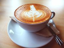 A Latte or cappuccino Coffee with latte art on the wooden desk Royalty Free Stock Photo