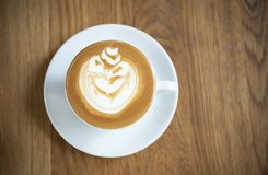 Latte or Cappuccino with frothy foam, coffee cup top view on wood table in cafe royalty free stock photos